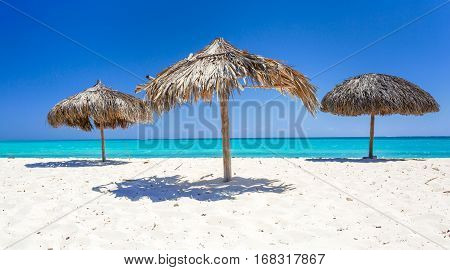 Beach Umbrellas made of palm leafs on the background of an exotic beach in Cayo Largo