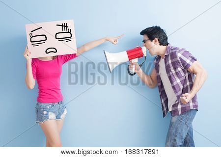man take the microphone shout to woman take confuse isolated on blue background