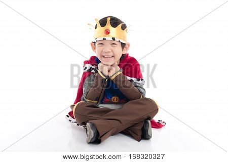 Little Asian boy prince with crown sitting on white background isolated