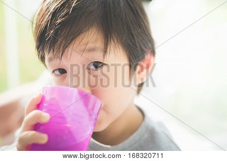Cute Asian child drinking water in the glassCute Asian child drinking water in the glass