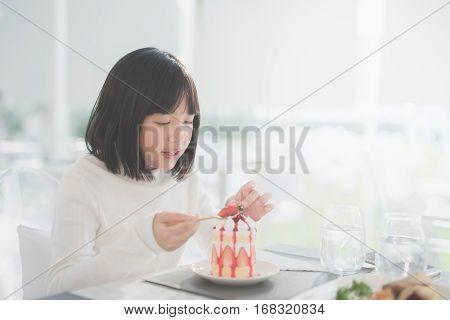 Beautiful Asian girl eating shortcake in a cafe