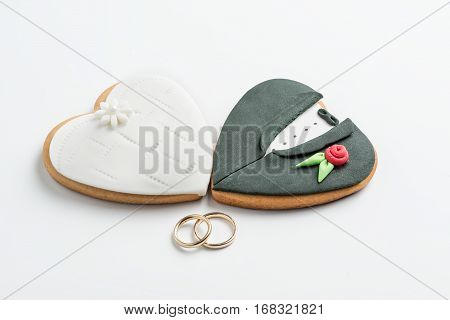 Bride and groom cookies and wedding bands on white background