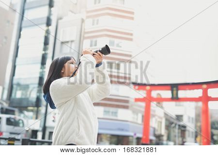Beautiful Asian girl with camera taking pictures in citytokyo japan