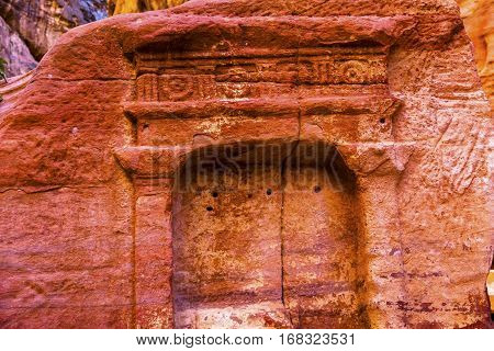 Tomb Outer Siq Canyon Petra Jordan Petra Jordan. Colorful Yellow Pink Canyon becomes rose red when sun goes down. The rose red can become blood red. Reds are created by magnesium in sandstone.