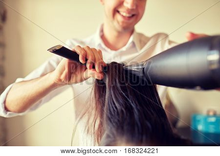 beauty, hairstyle, blow-dry and people concept -  close up of hairdresser with fan and brush making hot styling at hair salon