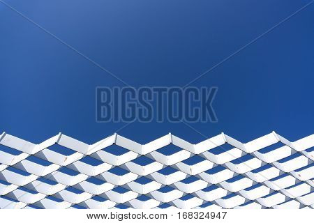 white steel mesh with blue sky background.