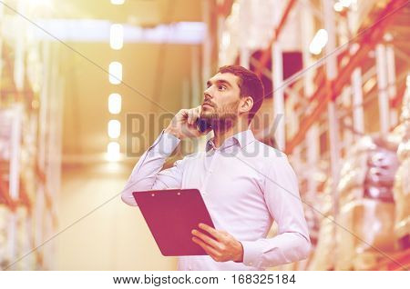 wholesale, logistic, business, export and people concept - businessman with clipboard calling on smartphone at warehouse
