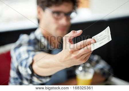 leisure, people, payment and finance concept - man with cash money paying at cafe