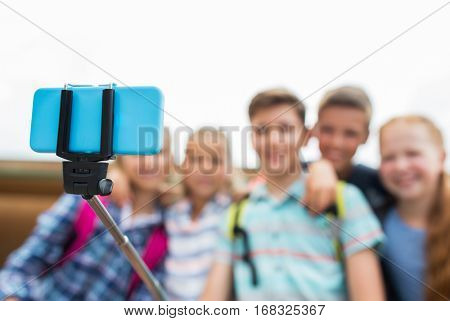 primary education, technology, friendship, childhood and people concept - group of happy elementary school students taking picture by smartphone on selfie stick outdoors