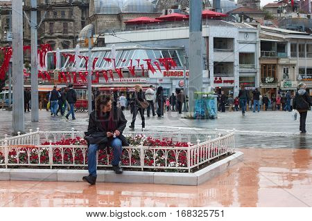 TURKEY, ISTANBUL - NOVEMBER 06, 2013: Unknown man resting on the Taksim Square. Taksim is a main transportation hub and a popular destination for tourists. Is also a favourite location for any events.