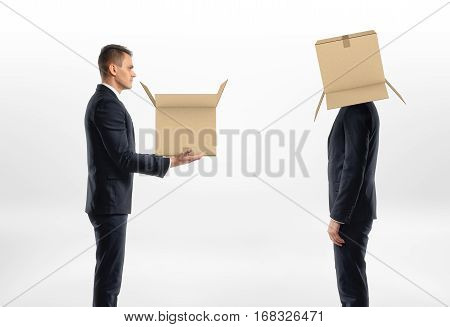 Businessman is passing a box to a man with a cardboard box on his head on white background. Business world. Communication at work. Fitting in.