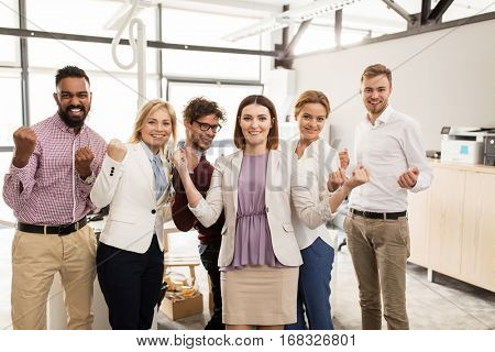business, triumph, gesture, people and teamwork concept - happy creative team showing fists and celebrating victory at office