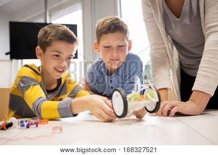 education, children, technology, science and people concept - happy boys and teacher building robot at robotics school lesson