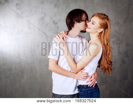 happy young couple hugging and kissing against old wall
