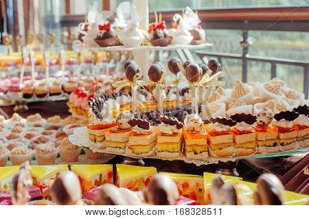 Catering at a luxury event with a wide choice of delicious gourmet desserts displayed on a long buffet table