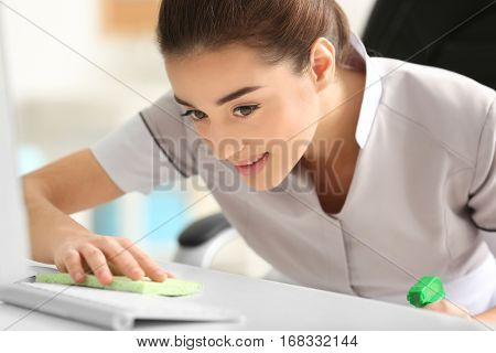Beautiful young charwoman wiping dust in office, closeup