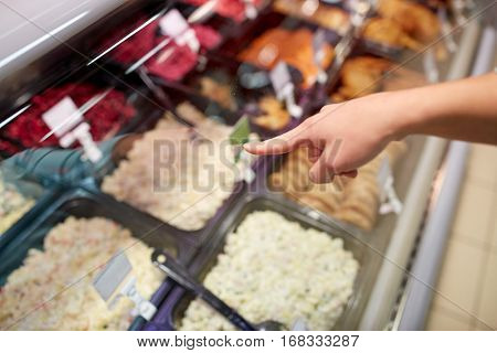people, shopping, sale and food concept - customer hand pointing at salads on grocery stall