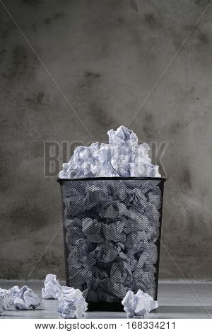 Concept. Creased paper in a trash can