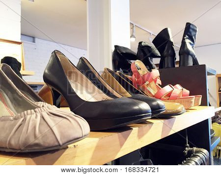 Stylish Shoes On Top Of A Clothing Rack