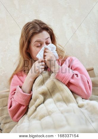 Young woman with flu and rhinitis lying in bed