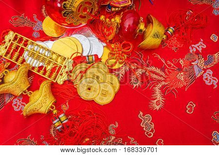 Chinese new year decoration on red fabric background ,Chinese characters text means: rich, successfully, happiness, peace, riches and honour, auspicious , good luck