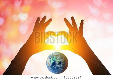 Earth And Hands Under A Heart-shaped Silhouette .blurred Background Of Valentine's Day Concept. Vale