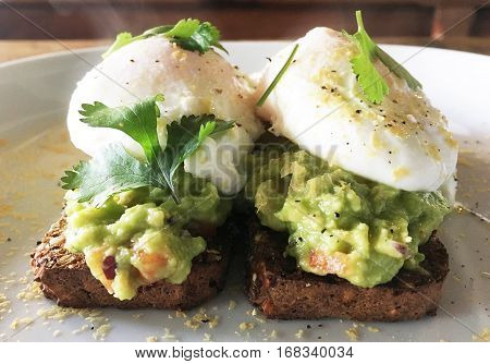 Avocado toast with poached eggs on a white plate