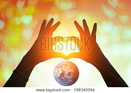 earth and hands under a heart-shaped Silhouette .Blurred background of Valentine's day concept. Pastel color tones.multicolored white  wall paper .