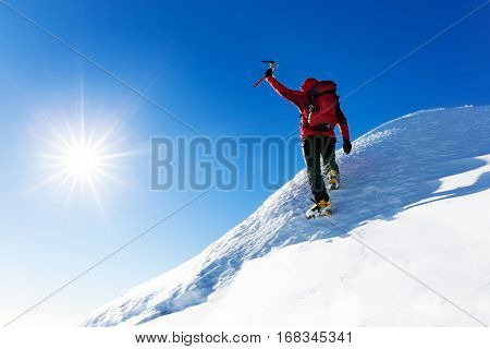 Extreme winter sports: climber reaches the top of a snowy peak in the Alps. Concepts: determination, success, strength.