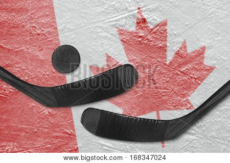 Hockey puck hockey sticks and the image of the Canadian flag on the ice. Concept