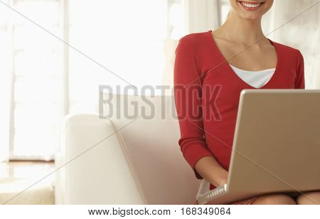 Happy young businesswoman with laptop sitting on chair in office lobby