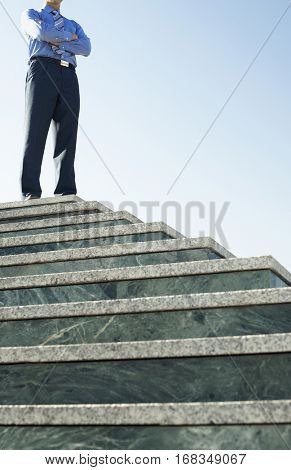 Low angle portrait of confident businessman standing on marble staircase against clear sky
