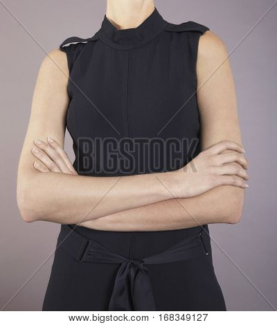 Portrait of a young businesswoman in black dress with arms crossed against purple background