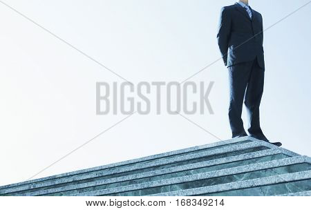 Low angle of confident businessman standing on marble staircase against clear sky