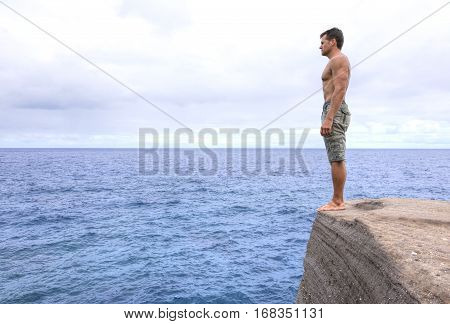 Muscular shirtless Caucasian man stands barefoot at edge of cliff overlooking big blue ocean on cloudy day