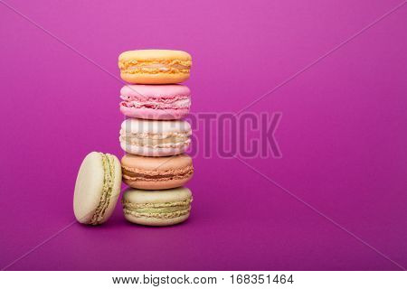 Sweet Colorful French Macaroon Or Macaron Biscuits On Purple Background