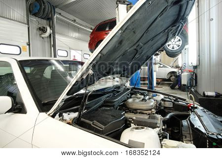 Car with open hood in a repair station