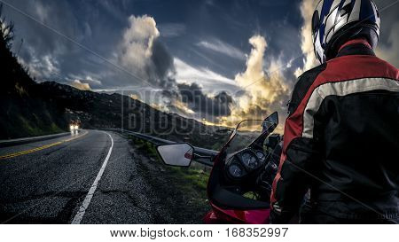 Male motorcyclist wearing protective leather racing suit with a red bike or motorcycle on an open road. The image is shot in HDR and composite. The vehicle is cropped to become generic non branded. The image depicts travel and adventure.