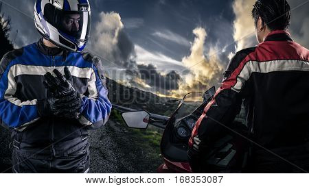 HDR composite of bikers or motorcycle riders with motor bikes on a road. The men depict a club or are competitors in a race. The image depicts racing and motorsports. The vehicle is cropped to be generic and non branded.