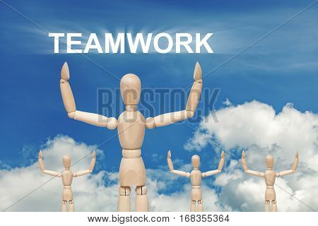 Wooden dummy puppet on sky background with word TEAMWORK. Abstract conceptual image