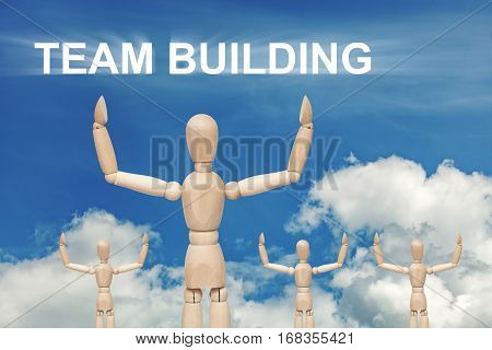 Wooden dummy puppet on sky background with word TEAMBUILDING. Abstract conceptual image