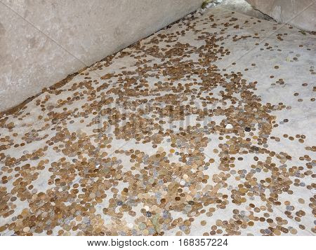Coins on a concrete floor. Throwing for luck and success of coins in the holy site.