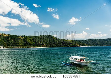 Small trimaran boat just outside the beach in Subic bay Philippines