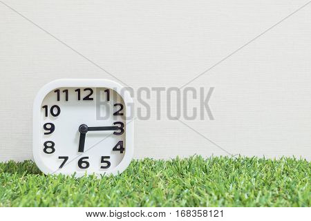 Closeup white clock for decorate show a quarter past six or 6:15 a.m. on green artificial grass floor and cream wallpaper textured background with copy space