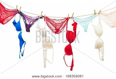Female panties and bra hanging on rope isolated on white background