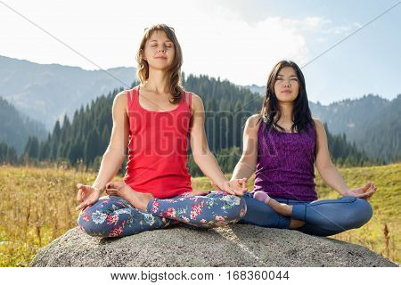 Two Young Women Doing Yoga On A Rock
