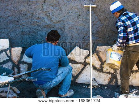 Construction site - workers wall cladding stone