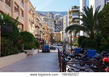 narrow street of densely populated district of Monaco, with green bushes and parking for motorcycles
