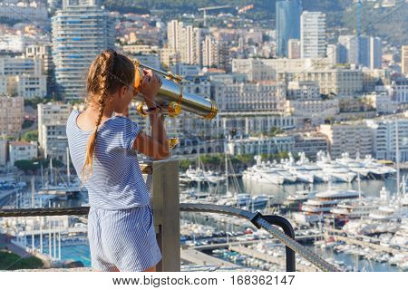 Girl looks through binoculars at observation from observation deck of palace Grimaldi
