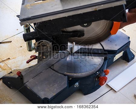 Closeup view wooden board electric circular saw. Focus is on the tools